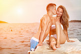 Young happy couple kiss on a beach during sunset