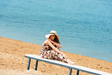 sweet girl on beach with hat resting