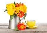 Colorful tulips bouquet in watering can and coffee cup