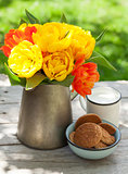 Colorful tulips bouquet, cookies and milk