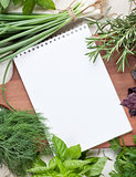 Fresh garden herbs and notepad for your recipe