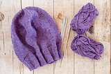wool purple hat, knitting needles and yarn