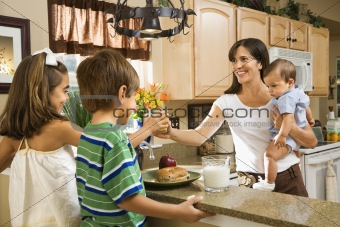 Mom giving kids breakfast.
