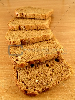 Five slices of brown bread with whole crop grains.