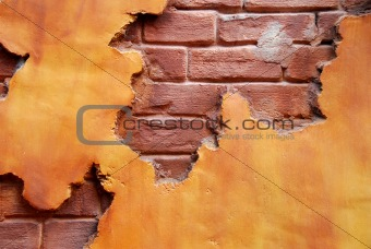 An orange colored stucco wall exposing red brick beneath and makes a great backgroud