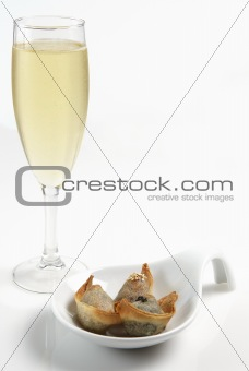A glass of champagne with finger food