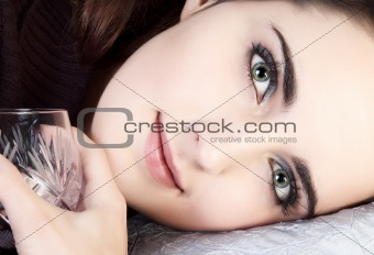 Beautiful girl face closeup with an empty wine glass