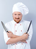 Head-cook holding two knives and looking at camera