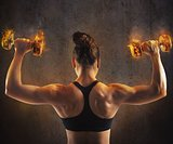 Woman training with  fiery dumbbells