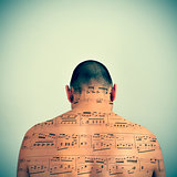 man with a musical score patterned in his back, with a retro eff