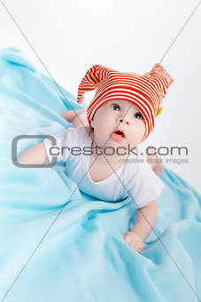 toddler in a striped hat on a blue blanket