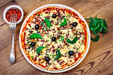 Pizza homemade with sauce on wooden background