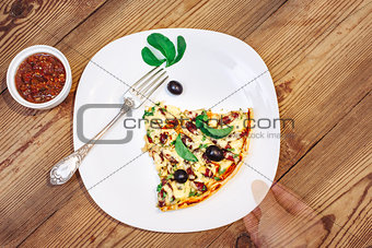 Slise of Pizza homemade with sauce on wooden background and arm