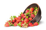 Scattered ripe juicy strawberries in a ceramic bowl