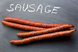 dried sausages on chalkboard