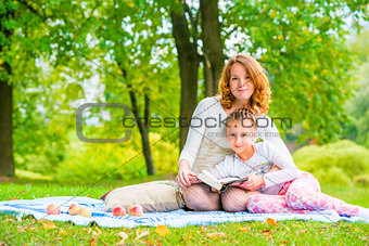 Beautiful mother and daughter spend a weekend at a picnic in the
