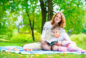 Mom and daughter in the park reading a book
