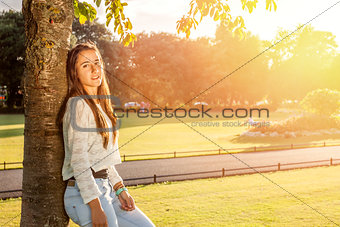 Beautiful teenager leaning on a tree