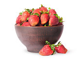 Ripe juicy strawberries in a ceramic bowl and two near