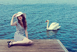 romantic girl near a swan on lake