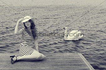 BW image of romantic girl near a swan on lake