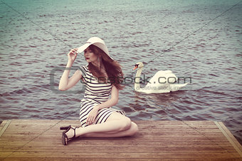 cute girl with hat and near a swan . vintage color