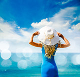 Woman in Blue Dress and Hat at Sea. Back View.
