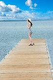 dreaming girl in elegat dress on lakes pier