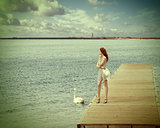 girl on pier with swan. vintage color
