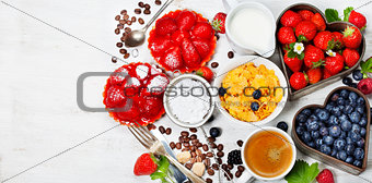 Breakfast with coffee, corn flakes, milk, tartlets and berry