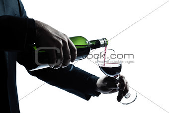 close up man hands pouring red wine in a glass  silhouette