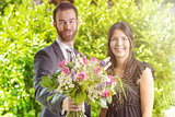 Young Couple at the Garden with Bouquet of Flowers