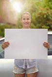 Woman Holding Empty White Board in front of her Car