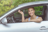 Smiling Young Woman in her Car Holding Keys
