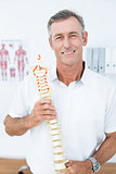 Smiling doctor showing anatomical spine