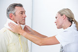 Doctor examining patient wearing neck brace