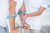 Doctor helping her patient walking with crutch