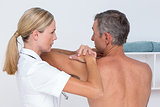 Doctor examining her patient shoulder