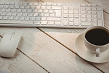 White keyboard and cup of coffee