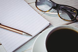 Empty notepad with reading glasses and cup of coffee