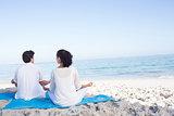 Happy couple doing yoga beside the water