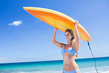 Pretty blonde woman holding surf board