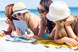 Happy friends wearing sun glasses and using tablet