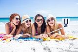 Happy friends wearing sun glasses and taking selfie