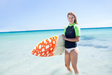 Fit blonde woman standing in the water and holding surfboard