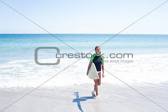 Fit blonde woman walking in the water and holding surfboard