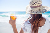 Brunette wearing straw hat and holding a cocktail