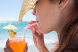 Brunette wearing straw hat and drinking a cocktail
