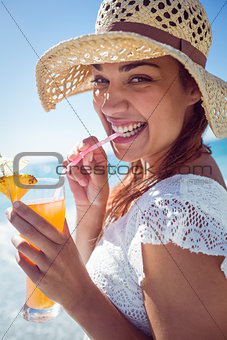 Smiling brunette wearing straw hat and drinking a cocktail