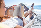Brunette reading a book while relaxing in the hammock
